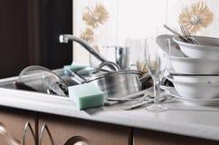 巨大的堆未洗的盘在厨房水槽和在工作台面 很多器物和厨房器具在洗涤前 免版税库存照片