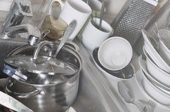 巨大的堆未洗的盘在厨房水槽和在工作台面 很多器物和厨房器具在洗涤前 库存图片