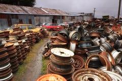 巨大的堆车轮和被击毁的汽车在废品旧货栈 免版税库存照片