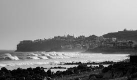 巨大的小组波浪在城市咆哮与一个多岩石的海滩在白天 免版税库存照片