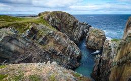 巨大的岩石和冰砾露出沿海角Bonavista海岸线在纽芬兰,加拿大 免版税库存照片