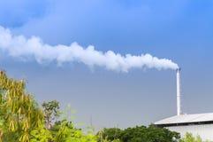 巨大的工厂烟囱污染空气的,散发水蒸气和烟污染的高烟囱 免版税库存照片