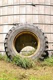 巨大的拖拉机轮胎在筒仓倾斜 库存图片