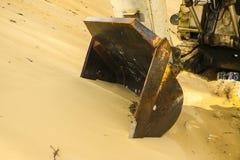 巨大的挖掘机桶开掘在沙子猎物采矿的沙子 免版税库存图片