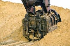 巨大的挖掘机桶开掘在沙子猎物采矿的沙子 免版税库存照片