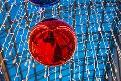 巨大的明亮的垂悬在购物中心的圣诞节红色球 库存图片