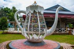 巨大的白合金水壶 五颜六色的挂锁心形在被弄脏的背景,爱的标志 沙巴,婆罗洲,马来西亚 库存图片