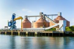 巨大的筒仓和其他港口设施在清楚的天空下 免版税库存图片