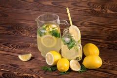 巨大的水罐和玻璃充分新鲜的夏天柠檬水用黄色,成熟和水多的柠檬和新鲜的绿色薄菏在一张黑暗的木桌上 库存照片