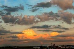 巨大,蓬松云彩,突出由在buildin上的朝阳 免版税库存图片