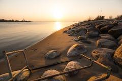 巨石城与清楚的天空和美好的生动的温暖的颜色的海滩日落 库存图片