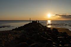 巨石城海滩与生动的红色和橘黄色的码头日落在波儿地克的海Tuja,拉脱维亚- 2019年4月13日 图库摄影