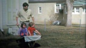 巨石城, CO 美国- 1974年:推挤孩子的爸爸在独轮车的围场附近 影视素材