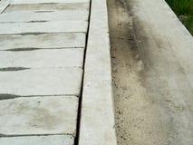 巩固下水道孔形式沿水泥路的一个样式 免版税库存图片
