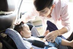 巩固汽车座位的父亲婴孩 免版税库存照片