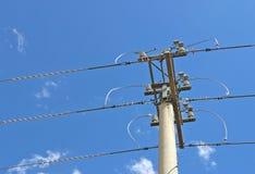 巩固电源杆和三条输电线在多云蓝天 图库摄影