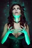巫婆创造魔术 有神秘的光的美丽和性感的妇女 库存图片