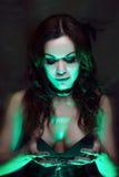 巫婆创造魔术 有神秘的光的美丽和性感的妇女 免版税库存照片