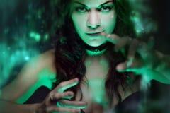 巫婆创造魔术 有神秘的光的美丽和性感的妇女 库存照片
