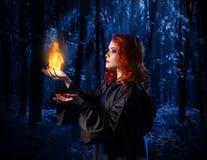 巫婆在有火焰的月光森林里 免版税库存照片