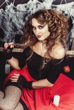 巫婆女孩万圣夜画象坐与黑墙壁的地板和在背景上的蜘蛛网 穿女衬衫和 库存照片