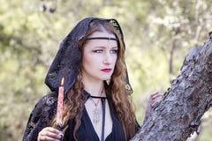 巫婆妇女在万圣夜期间在森林里 库存图片
