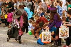 巫婆实施糖果对孩子在万圣夜游行 免版税库存照片