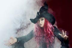 巫婆帽子的可爱的妇女有红色头发的执行魔术 烟和巫术 免版税库存照片