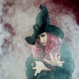 巫婆帽子的可爱的妇女有红色头发的执行魔术 烟和巫术 免版税库存图片