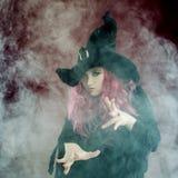 巫婆帽子的可爱的妇女有红色头发的执行魔术 烟和巫术 库存图片