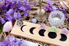 巫婆异教的月亮逐步采用有水晶、花和五芒星形的法坛 免版税库存图片