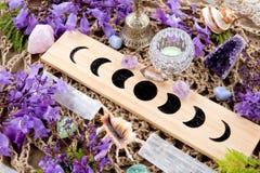 巫婆异教的月亮逐步采用有水晶和花的法坛 免版税库存图片