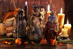 巫婆有蜡烛和古老纸纸卷的葡萄酒瓶 免版税库存照片