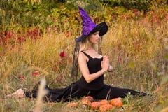 巫婆服装实践的瑜伽的俏丽的妇女 免版税库存照片