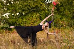 巫婆服装实践的瑜伽的女孩 库存照片