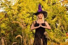 巫婆服装实践的瑜伽的好女孩 免版税库存照片