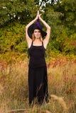 巫婆服装实践的瑜伽的好妇女 免版税库存照片