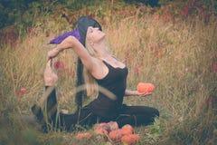 巫婆服装实践的瑜伽的妇女 免版税库存图片