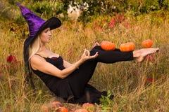 巫婆服装实践的瑜伽的年轻高兴的女孩 免版税库存图片