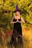 巫婆服装实践的瑜伽的微笑的女性 免版税库存图片