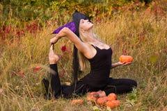 巫婆服装实践的瑜伽的微笑的妇女 库存图片