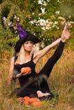 巫婆服装实践的瑜伽的快乐的女孩 免版税库存图片