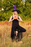 巫婆服装实践的瑜伽的快乐的女性 免版税库存图片