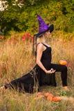 巫婆服装实践的瑜伽的快乐的妇女 免版税图库摄影