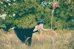 巫婆服装实践的瑜伽的愉快的女孩 库存照片