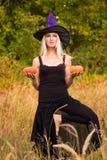 巫婆服装实践的瑜伽的愉快的女性 库存图片