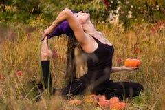 巫婆服装实践的瑜伽的愉快的妇女 图库摄影