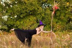 巫婆服装实践的瑜伽的成人女孩 免版税图库摄影