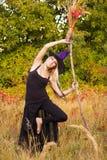 巫婆服装实践的瑜伽的活跃女性 免版税库存照片