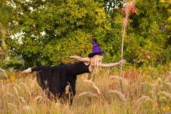 巫婆服装实践的瑜伽的白肤金发的女孩 免版税库存照片